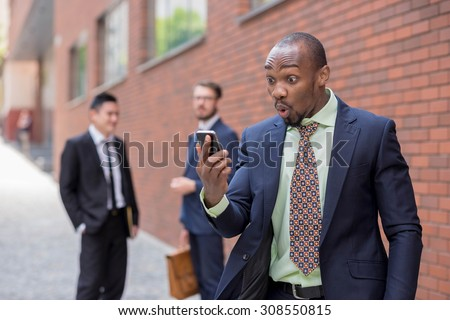 Portrait of multi ethnic business team. Three happy smiling men standing against the backdrop of the city. The surprised African-American man  talking on the phone , other is Chinese and European - stock photo