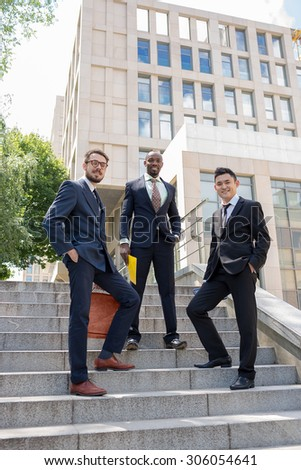 Portrait of multi ethnic business team.Three smiling men standing against the background of city. The one man is European, other is Chinese and African-American.  - stock photo
