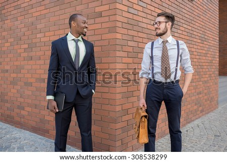 Portrait of multi ethnic business team. Two happy smiling men standing against the backdrop of the city. The one man is African-American, other is European. concept of business success and old and new - stock photo