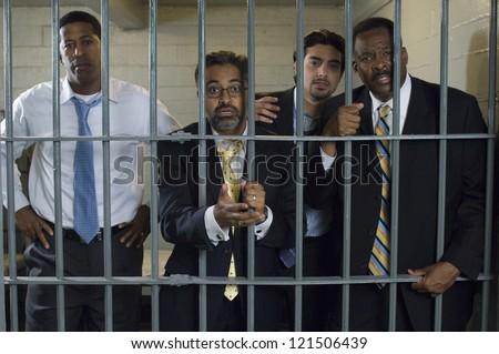 Portrait of multi ethnic businessmen caught behind prison gate - stock photo