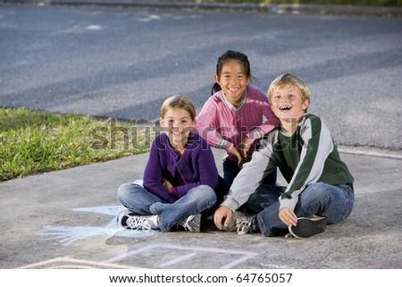 Portrait of multi-ethnic kids sitting together.  Girls 7 year, boy 9. - stock photo