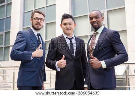 Portrait of multi ethnic successful business team holding their thumbs up. Three  men hands showing thumbs up against the backdrop of the city. The one man is European, other is Chinese and African - stock photo