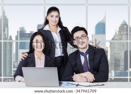 Portrait of multi ethnic teamwork sitting in the office with formal suit and laptop computer on desk - stock photo