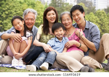 Portrait Of Multi-Generation Chinese Family Relaxing In Park Together - stock photo