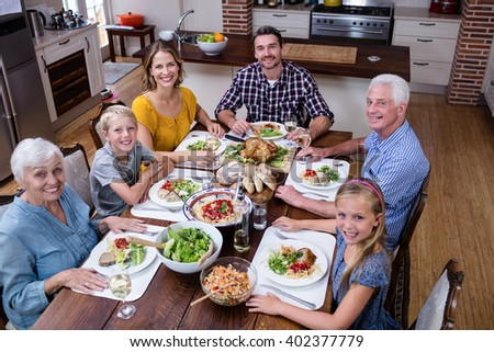Portrait of multi-generation family having meal in kitchen at home - stock photo