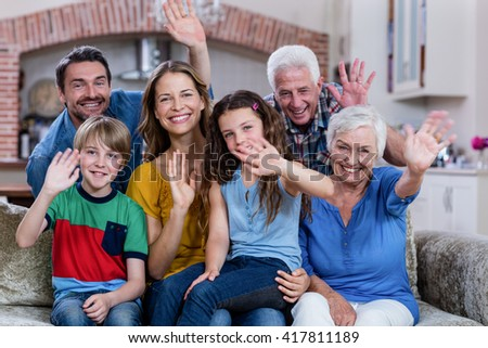 Portrait of multi-generation family sitting on sofa and waving hand at home - stock photo
