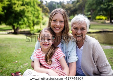 Portrait of multi-generation family sitting together in the park - stock photo