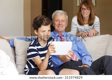 Portrait of multi-generation group sitting at home and have fun. Young teenager boy holding hand digital tablet and playing online while his mother and grandfather looking him.