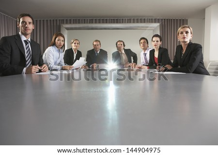 Portrait of multiethnic business people watching presentation in conference room - stock photo