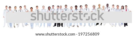 Portrait of multiethnic doctors holding blank banner against white background - stock photo