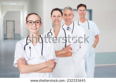 Portrait of multiethnic doctors with arms crossed standing in row at hospital corridor