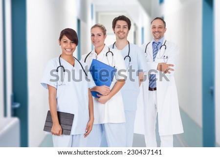 Portrait of multiethnic doctors with stethoscopes around neck standing in hospital corridor - stock photo