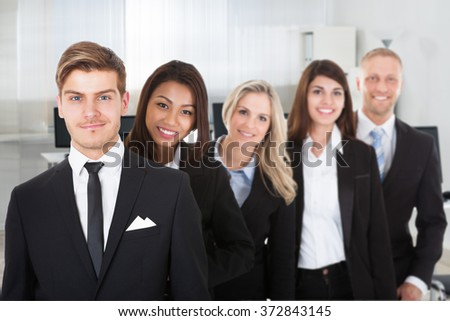 Portrait of multiethnic male and female professionals standing in row at office