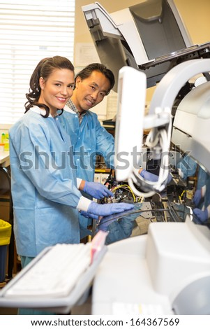 Portrait of multiethnic researchers smiling while working together in laboratory - stock photo