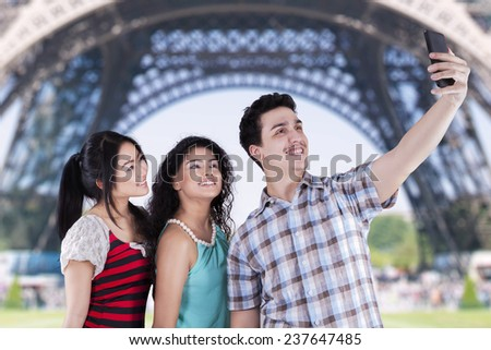 Portrait of multiracial teenagers using smartphone to take self portrait near the Eiffel Tower - stock photo