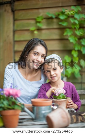 Portrait of mummy and her little girl doing gardening - stock photo