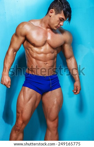 Portrait of muscle man on blue backgroud. - stock photo