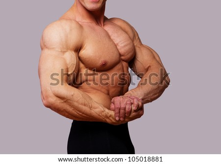 Portrait of muscle man posing on grey backgriund - stock photo