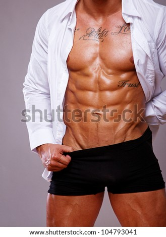 Portrait of muscle man torso on grey background - stock photo