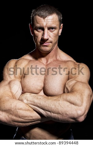 Portrait of muscular bodybuilder, isolated on black - stock photo