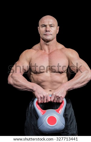 Portrait of muscular fit man lifting kettlebell against black background - stock photo