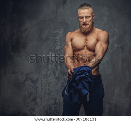 Portrait of muscular guy with beard in blue sports pants isolated on grey background.