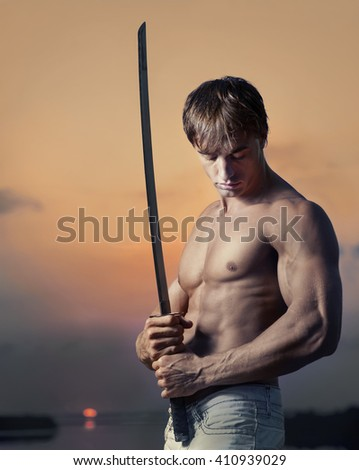 Portrait of muscular handsome guy with sword at sunset - stock photo