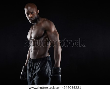 Portrait of muscular male boxer with boxing gloves against black background. Professional boxer looking at camera. - stock photo