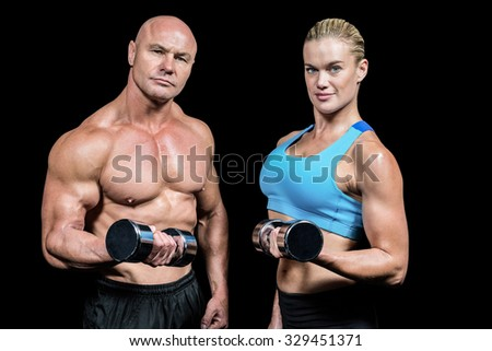 Portrait of muscular man and woman lifting dumbbells against black background - stock photo