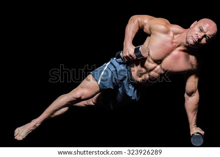 Portrait of muscular man exercising with dumbbells in side plank pose against black background - stock photo