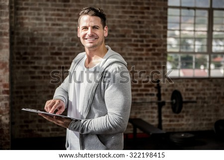 Portrait of muscular man holding clipboard at the gym - stock photo