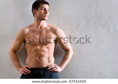 Portrait of muscular man leaning against the wall