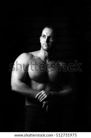 Portrait of muscular man standing with his hands on hips looking away with an attitude. Strong young man posing confidently. Black and white photography. Low key. Gym. Monochrome. Isolated on black.
