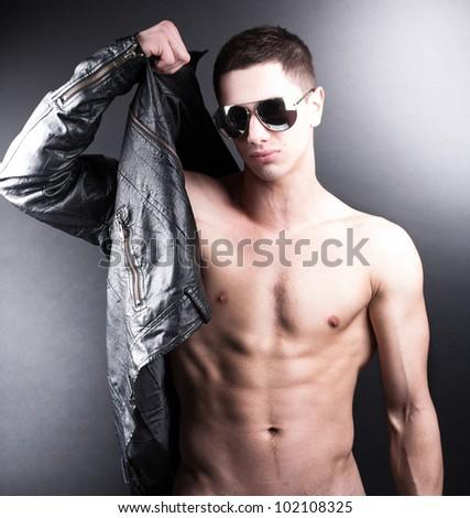 Portrait of muscular man wearing black leather coat - stock photo