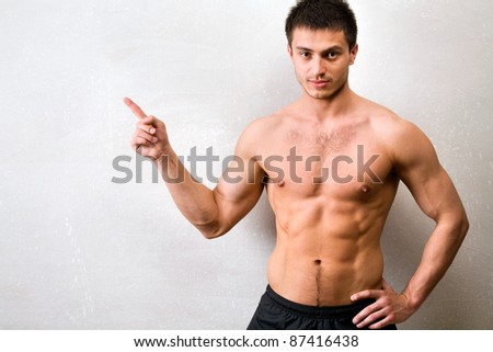 Portrait of muscular man who is pointing a finger at a gray wall - stock photo