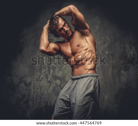Portrait of muscular shirtless male on grey background.