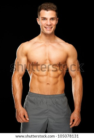 Portrait of muscular sporty man standing on black background - stock photo
