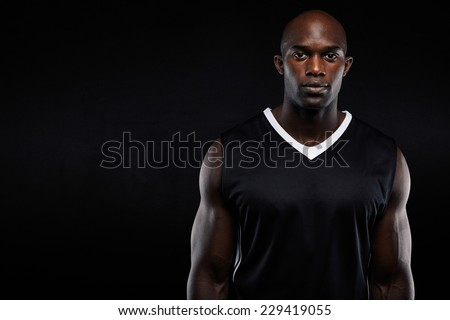 Portrait of muscular young man in sportswear looking at camera against black background. Strong african athlete with copyspace - stock photo