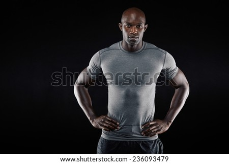 Portrait of muscular young man in sportswear standing with his hands on hips looking at camera against black background. Strong african athlete with copyspace. - stock photo