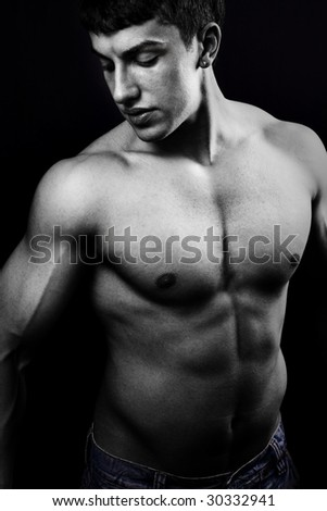 Portrait of muscular young man in the dark - stock photo