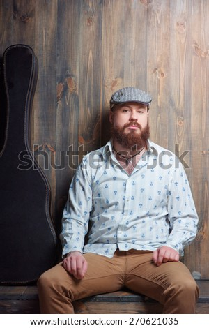 Portrait of musician. Handsome young bearded man sitting with guitar case over wooden background. - stock photo