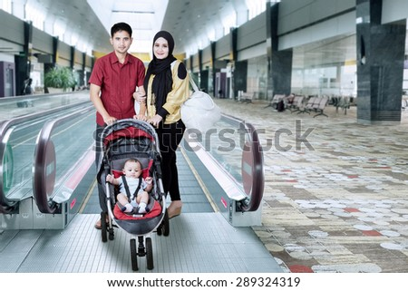 Portrait of muslim family standing in the airport hall near the escalator with baby on the pram - stock photo