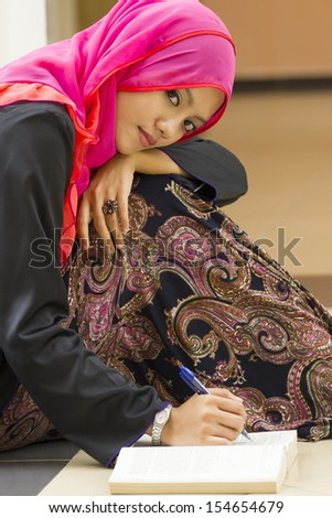 Portrait of muslim girl writing a  book  - stock photo