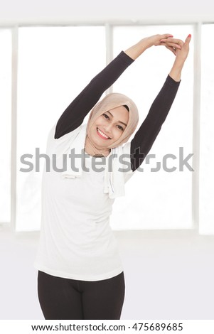 portrait of muslim sporty woman doing hand stretching