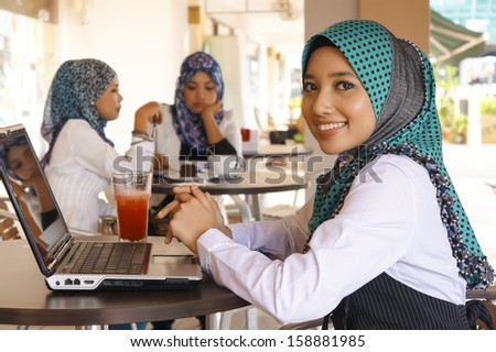 Portrait of Muslim Student wearing Scarf using Laptop at the Cafe  - stock photo