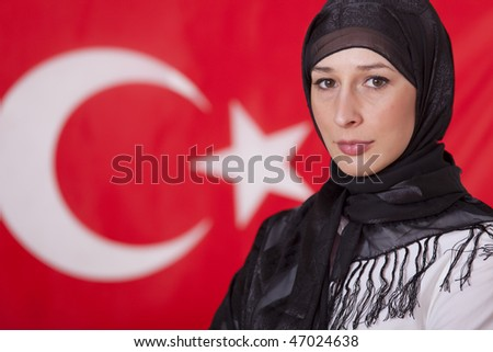 portrait of muslim woman in front of turkish flag - stock photo