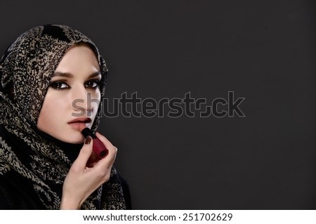 Portrait of Muslim woman painting her lips with a lipstick on gray background - stock photo
