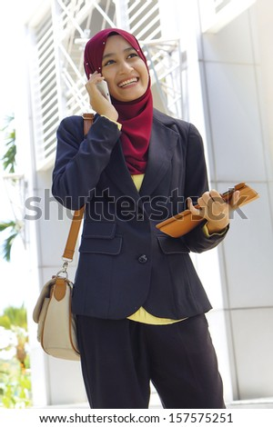 Portrait of Muslim woman wearing Hijab outdoor using mobile phone - stock photo