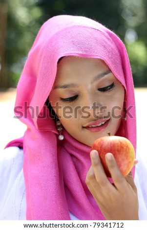Portrait of muslim woman with apple - stock photo