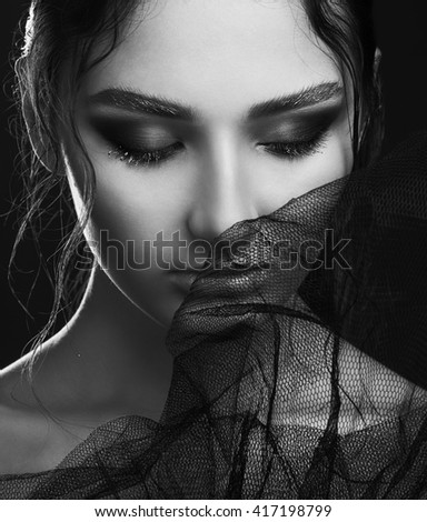 Portrait of mysterious beautiful brunette  through black veil and posing over black background. Gold eyebrows, wet lips, red shadows. Close up. Vogue style. Studio shot. Haute couture concept.  - stock photo